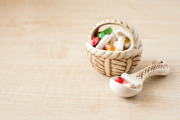 Many different colored pills, tablets and capsules in ceramic vase, bowl, basket and spoon on wooden background. Assorted pharmaceutical medicines, drugs. Selective focus. Copy space.