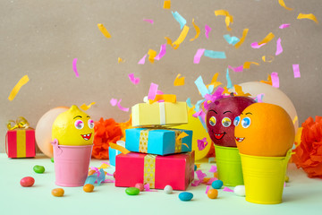 Funny attractive fruits with eyes and mouth - apple, orange, lemon, enjoy the gifts and dance on festive background. Summer party celebration vacation concept. Happy birthday, Family holiday