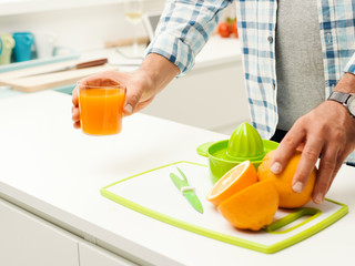 Man preparing fresh orange juice