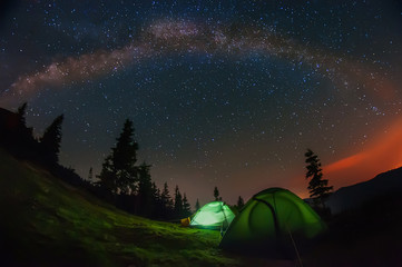night photo in the mountains. Tents in the clearing under the starry sky, the milky way to the whole sky above the tents and mountains.