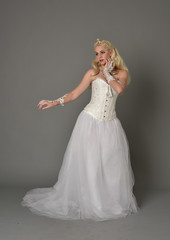 full length portrait of blonde girl wearing white corset gown. standing pose on grey studio background.