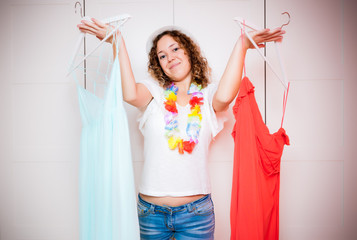Woman can not choose which clothes pack for travel. Standing her clothes in front of a wardrobe