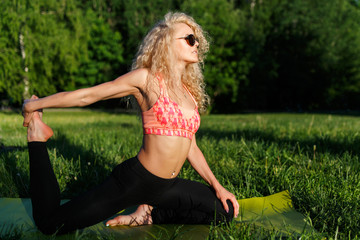 Picture of young curly-haired sports woman practicing yoga on rug in park