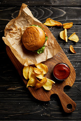 Top view of set of junk food with burger and potatoes served on wooden board