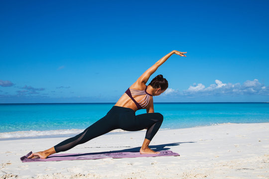 Beautiful young woman practicing yoga ion the beach on Bahamas iseland.