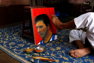 Ranjan Kurmi, 32, a fan of Argentina's football team paints footballer Lionel Messi's image on a canvas ahead of FIFA World Cup 2018 Group D match between Argentina and Iceland, inside a house on the outskirts of Kolkata