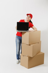 Full length of delivery woman in red cap, t-shirt isolated on white background. Female courier near empty cardboard boxes, laptop pc computer, blank black empty screen. Receiving package. Copy space.