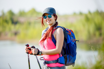 Image of sports woman with walking sticks and backpack on background of lake and vegetation