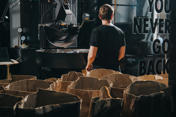 Man standing by paper bags with coffee beans in industrial coffee shop