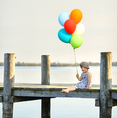 Mädchen mit bunten Luftballons am Steg