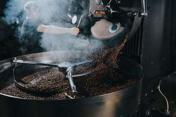 Professional male roaster loading machine with coffee beans