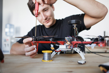 Picture of man with screwdriver fixing square copter at table