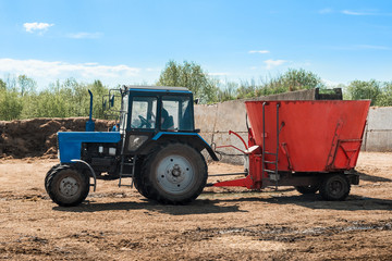 Tractor working on farm. Blue tractor pulling red trailer. Agricultural machine
