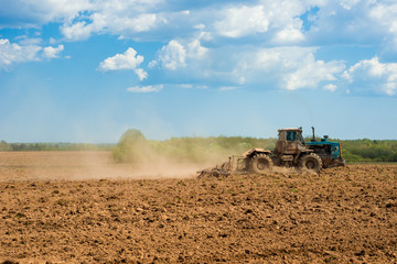 Tractor plowing a field on a sunny day. Preparing land for sowing. Agricultural works at farmlands. Tractor ploughing a field with a dust behind it. Agriculture industry