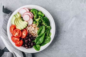 Burrito Buddha Bowl with wild rice and broccoli, spinach, black beans, tomatoes, avocado and radish