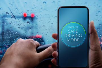 Drive with Safe Concept. Driver Switching Smartphone to Safety Mode. Rainy Day and Bad Weather on the Road with Blurred Lights and Traffic Jam in City