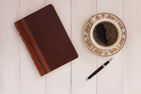 Cup of coffee, pen and notebook