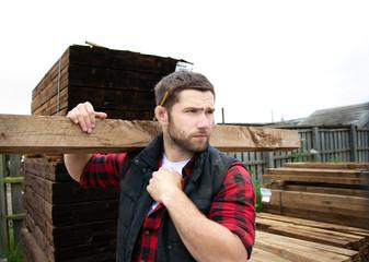 Lumber yard worker, carpenter, choosing, seclecting carrying timber planks