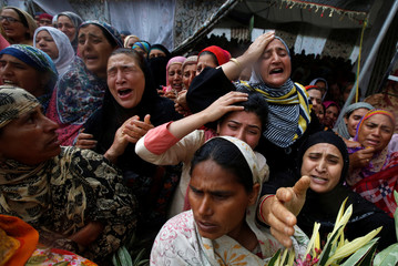 "Women mourn as people carry the body of Syed Shujaat Bukhari, the editor-in-chief of local newspaper ""Rising Kashmir"", who according to local media was killed by unidentified gunmen outside his office in Srinagar, during his funeral in Kreeri"