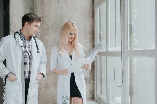 7cf172e2e94 Medical multiethnic staff having discussion in a hospital hallway. Male and  female nurse wearing blue scrubs working in a medical clinic. Two hospital  ...