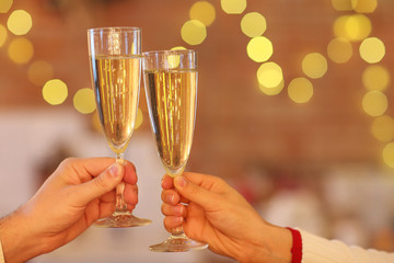 Two glasses of champagne over blur lights background.