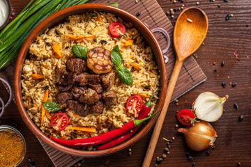 Uzbek restaurant concept, Uzbek food feast. Uzbek pilaf made from beef, lamb, chicken, in large earthenware, plate, next to vegetables. Copy space