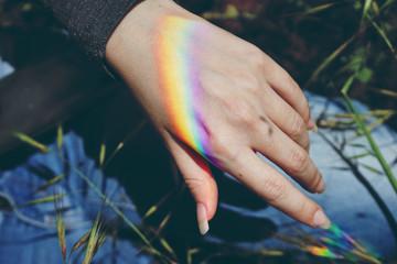 Arco iris proyectado en una mano pasando la luz solar a través de un prisma