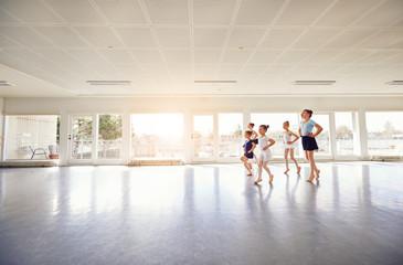 Group of little ballerinas performing ballet dance in class