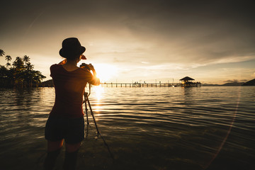 Female tourist take photograph of a beautiful sunset at sea, Koh Mak Thailand