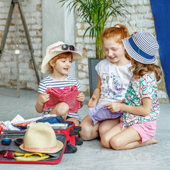 Three happy children pack their clothes in a suitcase. Square. Concept, lifestyle, childhood, trip, vacation, family tourism