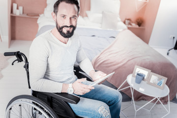 Good mood. Cheerful handicapped man sitting in a wheelchair and holding a tablet