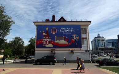 People walk in front of a billboard advertising the FIFA World Cup in Saransk