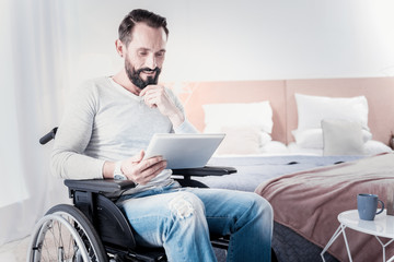 My leisure. Content handicapped man sitting in a wheelchair and holding a tablet