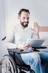 Pleasant talk. Happy crippled man sitting in a wheelchair and holding a tablet and waving