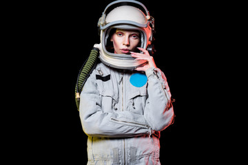 attractive female astronaut in spacesuit and helmet isolated on black