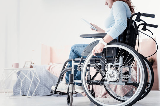 Interesting book. Smiling crippled woman sitting in the wheelchair and holding her book