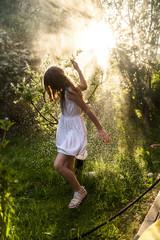 Girl having fun with garden hose in summer