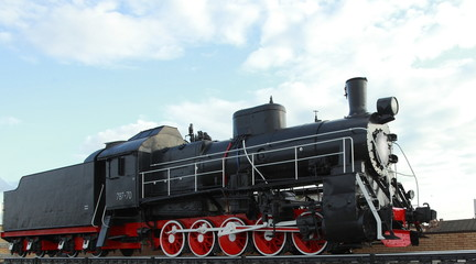 Black vintage steam locomotive with red wheels on the railway.