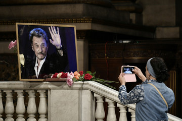 A fan takes a picture of a portrait of the late French singer Johnny Hallyday during a tribute mass the day he would have celebrated his 75th birthday, at the La Madeleine church in Paris