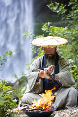 European man with beard and japanese robe makes fire ceremony in front of Great Waterfall in Austria