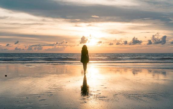 Silhueta de mulher caminhando para a luz, pôr do sol, Bali, Seminyak Beach, Indonesia