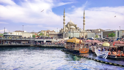 View from the water on the historical center of Istanbul. View of the Suleymaniye Mosque, Galata bridge, Eminonu district and square and Balik Ekmek boat shops.