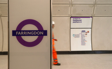 A Crossrail employee walks in the new Farringdon underground station of the Elizabeth line which opens in December 2018, in London