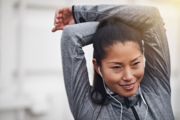 Sporty young Asian woman listening to music outside while stretc
