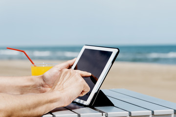 man using a tablet on the beach.