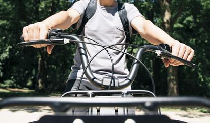 man riding a bike by a public park.