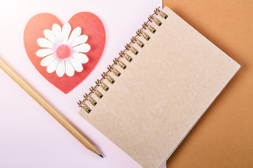 Blank diary and red heart with wooden pen.