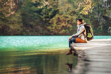 Woman traveler sits on wood bridge and looks calm on mountain lake at sunny autumn day