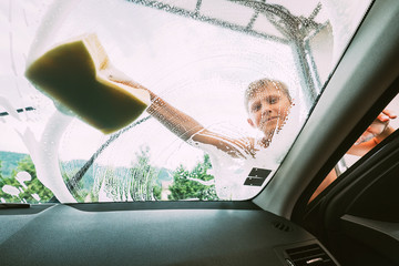 Boy washes front car window with sponge