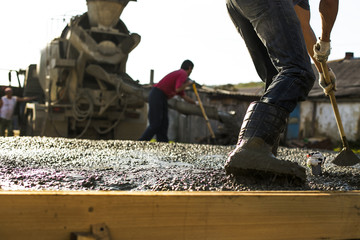 Construction workers are pouring a building foundation. Concrete works with the mixer truck and people with shovels. Mixer truck providing wet cement to the  wooden falsework on the construction site.